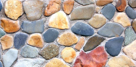 Stone wall of the house from different color of stones in a laying Stock Photo - 7987335