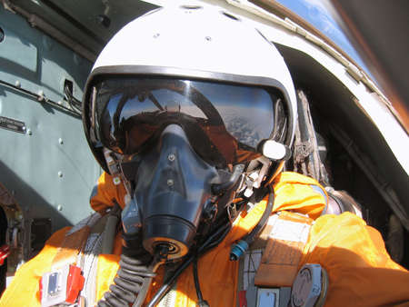 The military pilot in the plane in a helmet in dark blue overalls against the blue sky photo