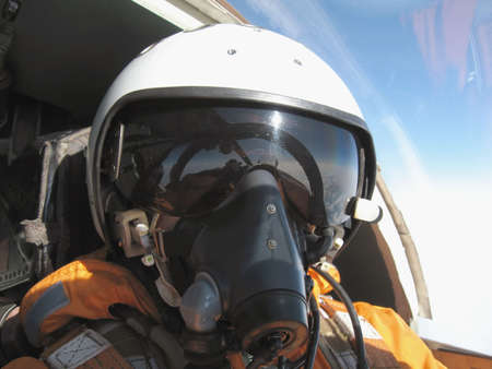 The military pilot in the plane in a helmet in dark blue overalls against the blue sky