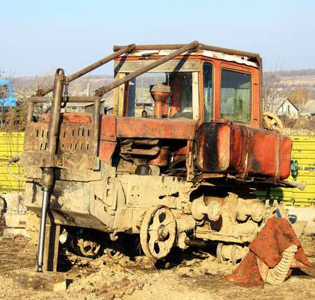 An old tractor standing on the field photo