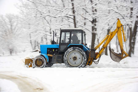 deletes: The tractor of dark blue color deletes snow in park Stock Photo