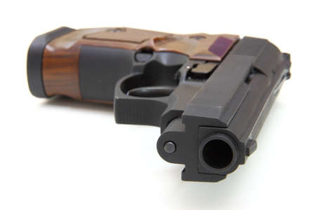 The close up of a pistol a target and cartridges is isolated on a white background Stock Photo