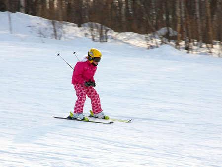 Little girl skiing downhill in winter equipment photo