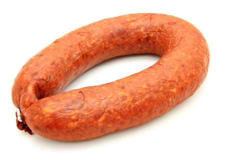 Tasty sausage is curtailed by a ring lies on a white background  photo