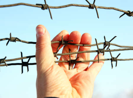 penal institution: Hand of prison and sky background Stock Photo