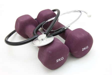 estetoscopio corazon: Estetoscopio y pesos de formaci�n mancuernas para conceptualizar un estilo de vida saludable.
