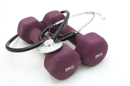 Stethoscope and dumbbell training weights together to conceptualize a healthy lifestyle.