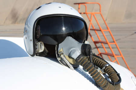 Protective helmet of the pilot against the plane with an oxygen mask on a fuel tank photo