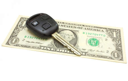 The car key lies on a dollar isolated on white in a background photo