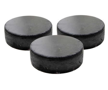 Three old black hockey puck isolated on white background. photo