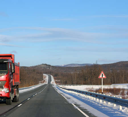 The red truck on a winter road. photo