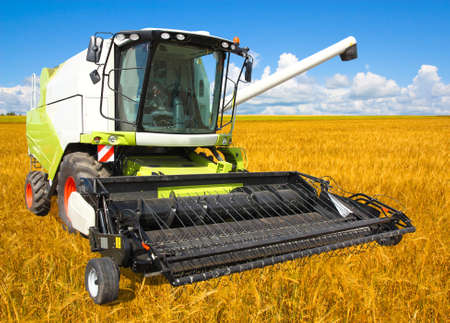 agricultural machinery: combine harvester on a wheat field with a blue sky Stock Photo