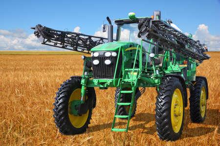 cosechadora: tractor pulverizador de cosechadora en un campo de trigo con un cielo azul
