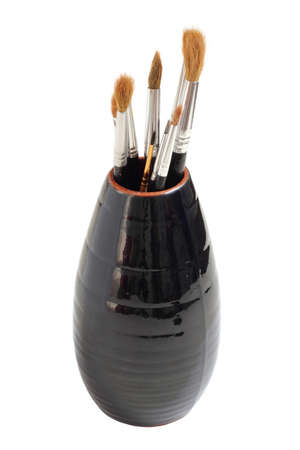 daubs: Vase with brushes of the artist on a white background