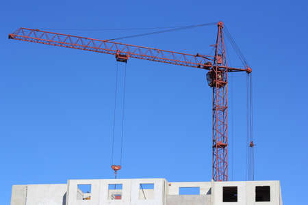red crane and blue sky on building site photo
