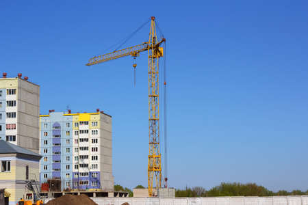 yellow crane and blue sky on building site photo