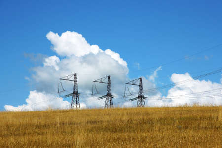 rousing: Three electrical towers  background of clouds and sky Stock Photo
