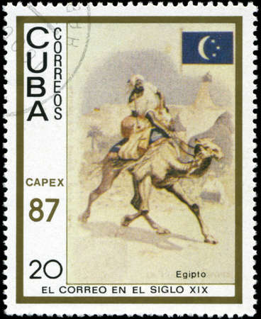 camel post: CUBA - CIRCA 1987: A stamp printed in the Cuba, shows traditional old vehicles. Egyptian camel, circa 1987 Stock Photo