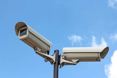 Two security cameras against blue sky Stock Photo