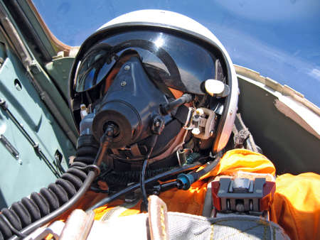 military pilot in the plane in a helmet in dark blue overalls against the blue sky photo