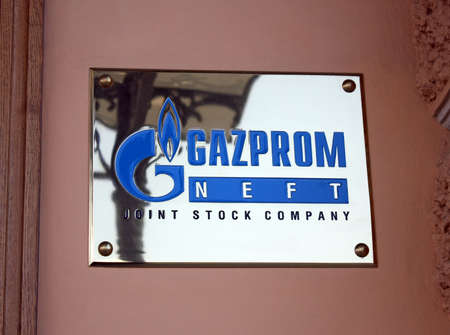 ST-PETERSBURG, RUSSIA, AUG 04, 2013: GAZPROM logo metal plate on the facade of building. Open Joint Stock Company Gazprom is the largest extractor of natural gas and one of the largest companies in the world