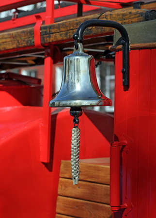 clang: Metal alarm bell on red fire truck.