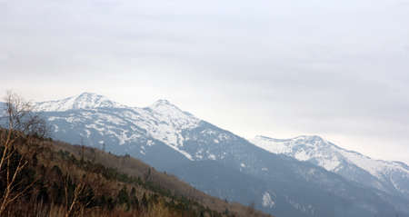 ridges: Mountain ridges covered with snow and overcast sky.