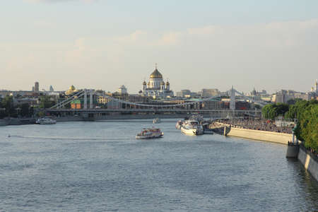 Moskva river with river buses from Novoandreevskiy Bridge. Krymsky bridge and Cathedral of Christ the Savior on the horizon in Moscow, Russia.