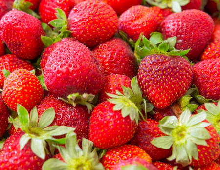 Background of beautiful and juicy strawberries with green leaves. Stock Photo
