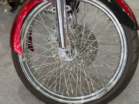 Beautiful nickel plated front wheel of a red motorcycle. Imagens