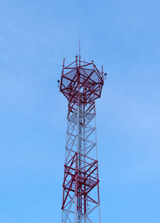 Telecommunication tower with antennas against with blue skyand white cloud background