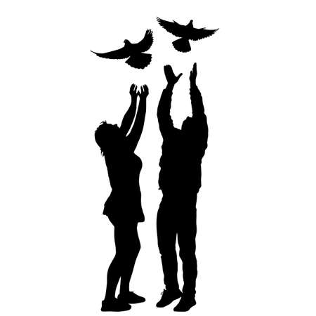 Silhouette of a guy and a girl letting go of the dove into the sky.