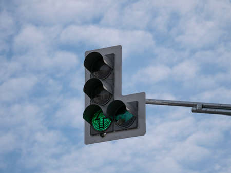 Green traffic light with an additional section against a cloudy sky. Фото со стока