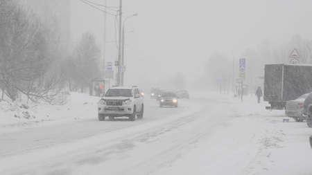 Śnieg w mieście na drodze z samochodami.
