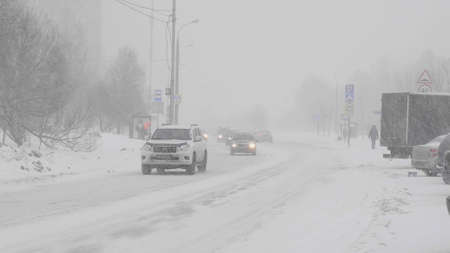 Snow in the city on the road with cars.