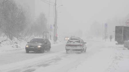 Schnee in der Stadt auf der Straße mit Autos. Standard-Bild