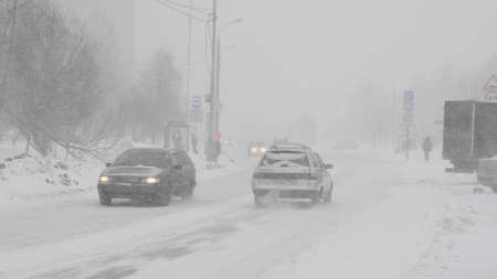 Snow in the city on the road with cars. 스톡 콘텐츠
