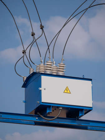 Electric transformer with wires and an insulator against the sky.