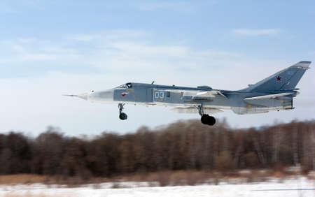 Military jet bomber Su-24 Fencer flying above ground.
