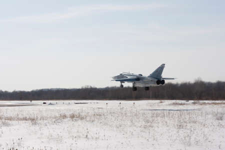 Military jet bomber Su-24 Fencer flying above ground. 免版税图像