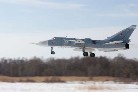 Military jet bomber Su-24 Fencer flying above ground. Publikacyjne