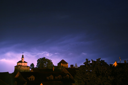 Lightning in a storm in old medival city with castle and a chapel (Kamnik, Slovenia) photo
