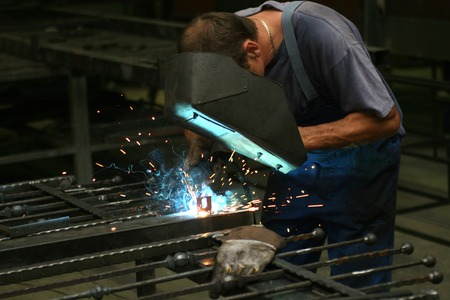 Welder in a workshop making a fence photo