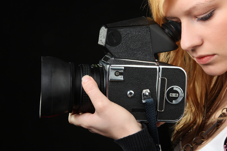 Attractive blonde girl photographing with medium format camera photo