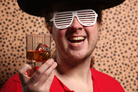 Crazy rock and rollerer with a big black hat, party glasses and a glass of whiskey in front of a cheetah skin background photo