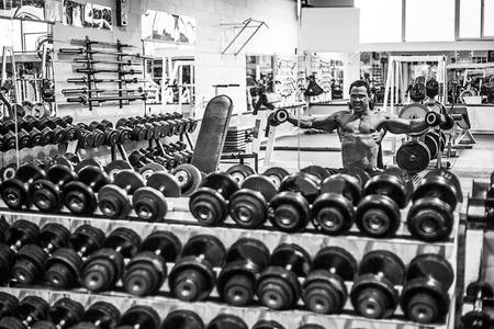 attractive male: Culturista masculino atractiva que ejercita en el gimnasio con pesas Foto de archivo