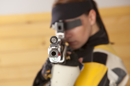 Woman training sport shooting with air rifle gun photo