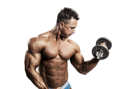 Muscular man exercising  with dumbbell photo