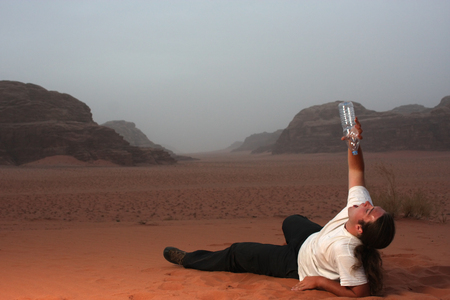 Desperate man in the desert drinking last drops of water from an empty bottle photo