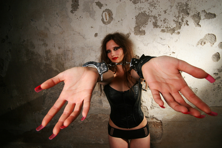 Sexy lady with handcuffs by the wall photo